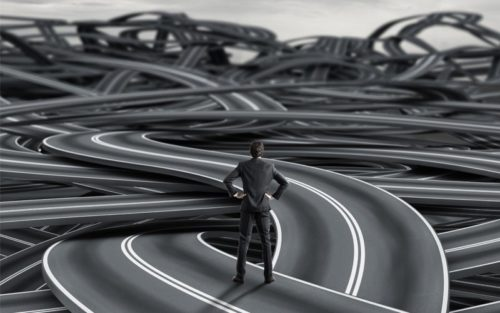 Man stands in front of a tangle of roads